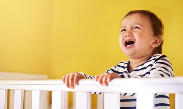 Cropped shot of a baby girl crying in her crib at home