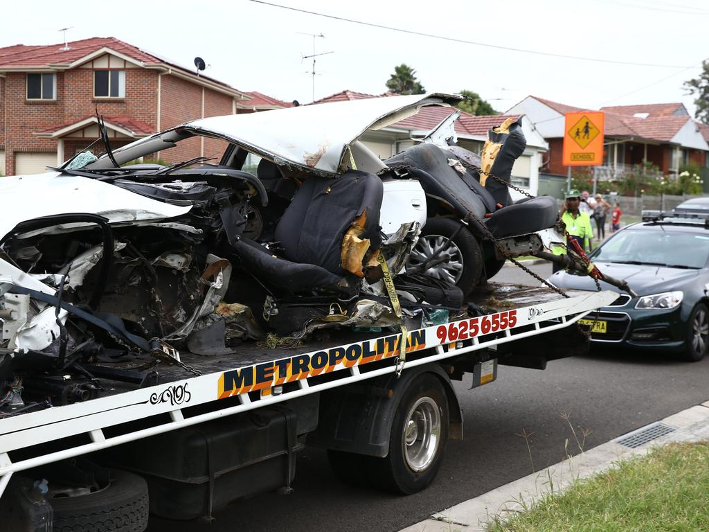 The mangled wreck on the back of a tow truck at the scene of the triple-fatal car crash.