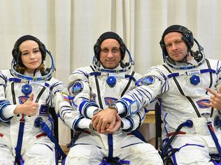 """This handout photo taken and released on October 5, 2021 by Russian Space Agency Roscosmos shows Russian crew members, cosmonaut Anton Shkaplerov (C), actress Yulia Peresild (L) and film director Klim Shipenko, shaking hands as their spacesuits are tested prior to the launch onboard the Soyuz MS-19 spacecraft at the Russian-leased Baikonur cosmodrome. - A Russian actress and director arrived at the International Space Station (ISS) on October 5, 2021 to begin a 12-day mission to make the first movie in orbit. The Russian crew is set to beat a Hollywood project that was announced last year by """"Mission Impossible"""" star Tom Cruise together with NASA and Elon Musk's SpaceX. (Photo by Andrey SHELEPIN / Russian Space Agency Roscosmos / AFP) / RESTRICTED TO EDITORIAL USE - MANDATORY CREDIT """"AFP PHOTO/ RUSSIAN SPACE AGENCY ROSCOSMOS"""" - NO MARKETING - NO ADVERTISING CAMPAIGNS - DISTRIBUTED AS A SERVICE TO CLIENTS"""