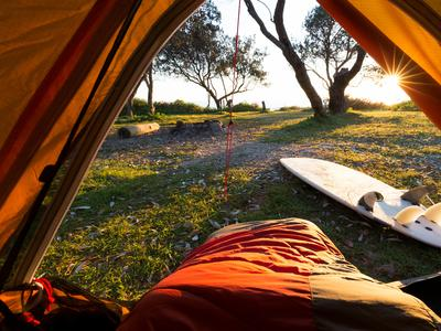 A hikers point of view from a tent, overlooking a bright morning and a surfboard.