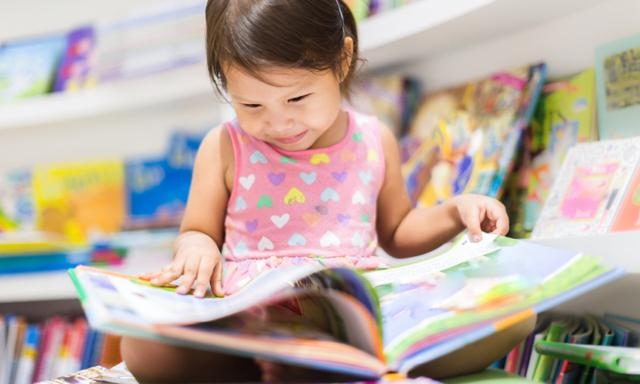 A happy child looking at a book in the library.
