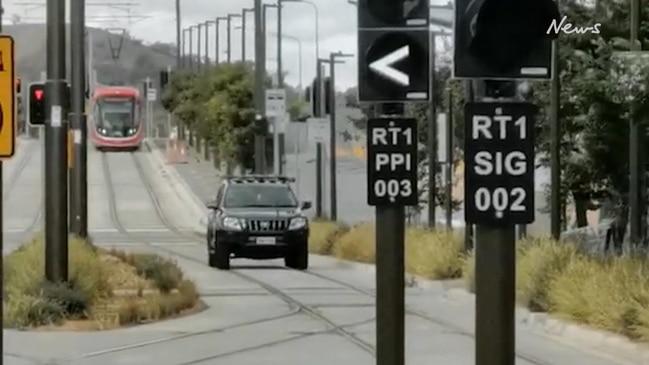 Car reverses in front of light rail on tracks