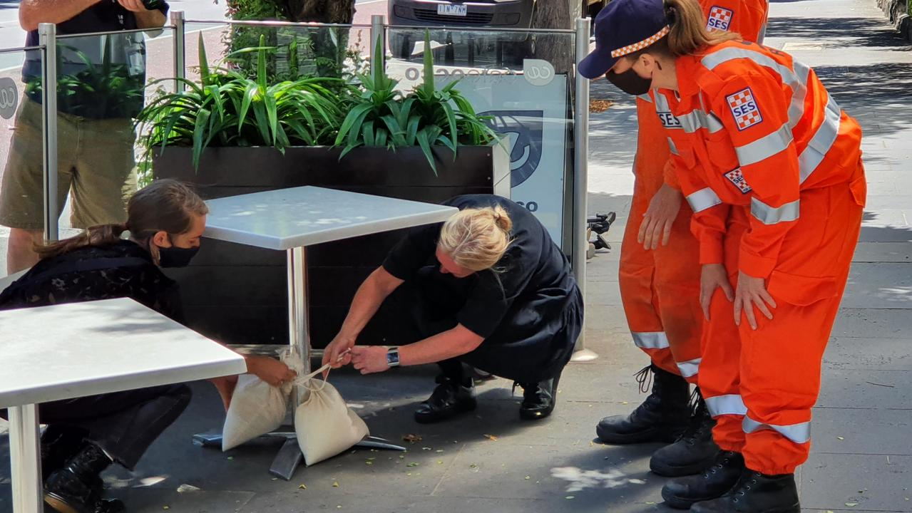 Victorian SES volunteers help cafe staff secure a coffee table in anticipation of damaging winds in Victoria on Saturday. Picture: Supplied