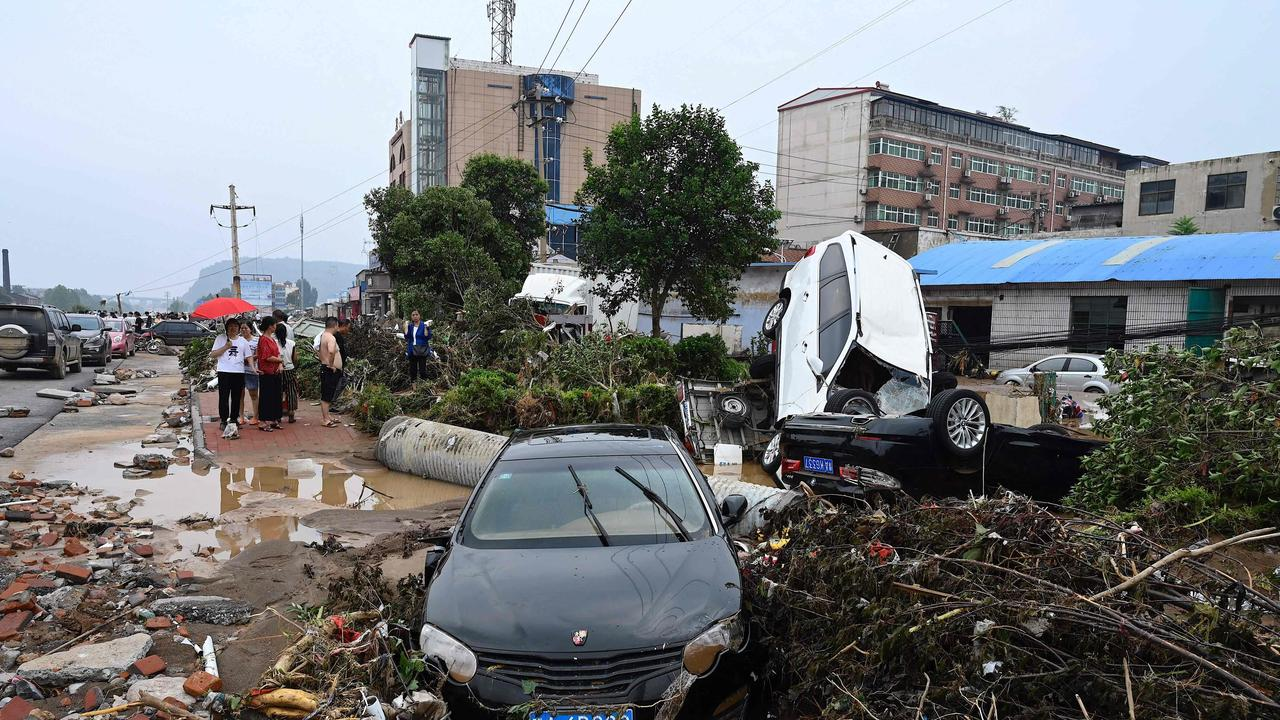 Damaged cars and uprooted trees after severe flooding and landslides. Picture: Jade Gao/AFP