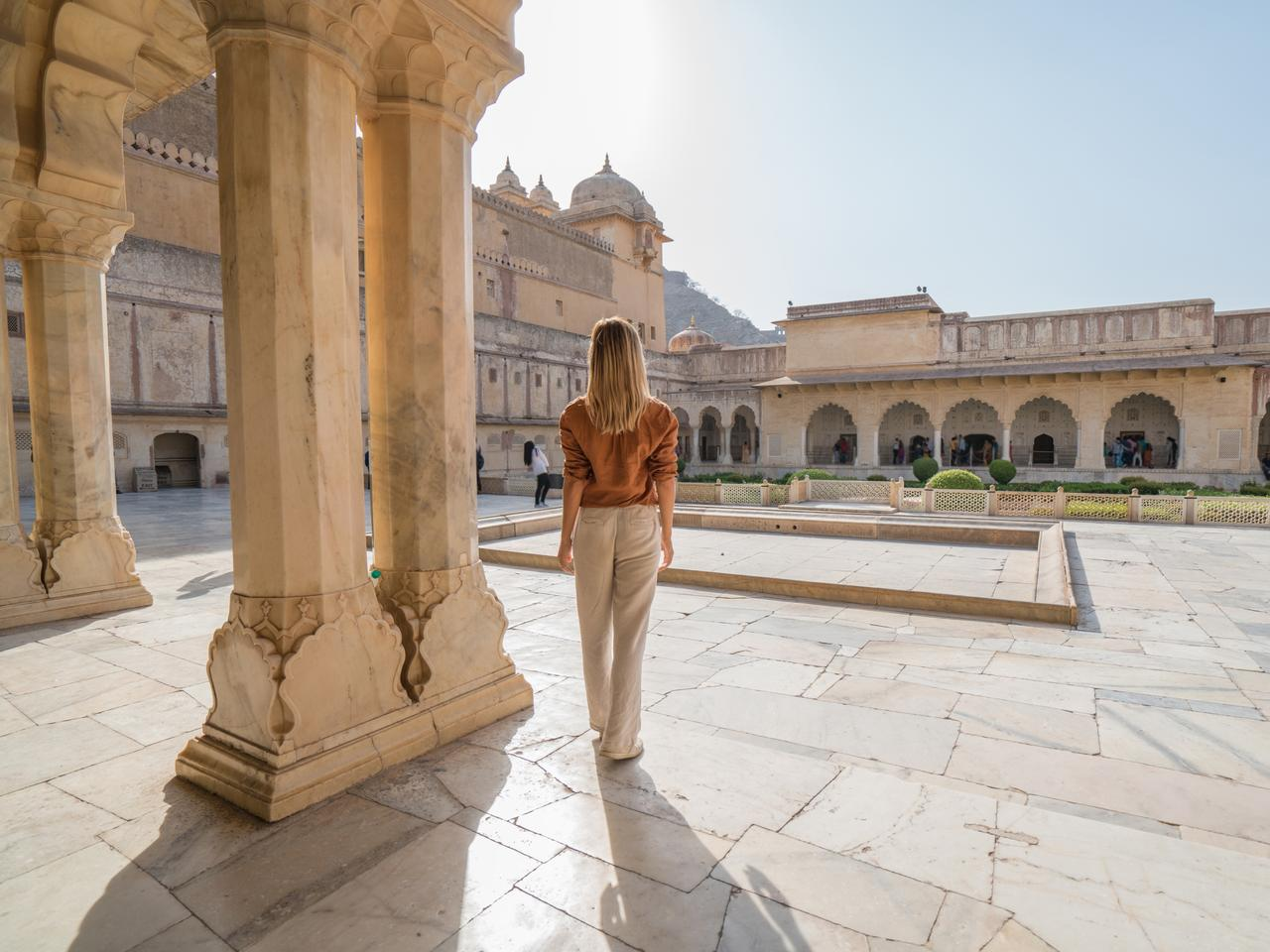 Young woman traveling in India contemplating ancient temple in Jaipur, India