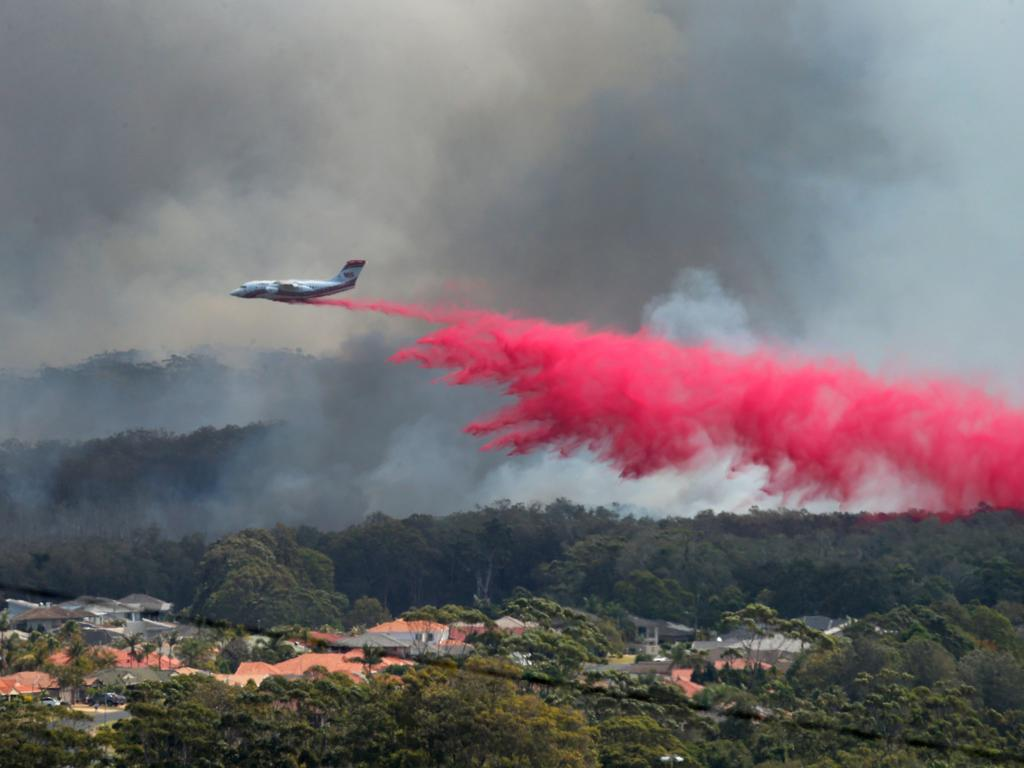 A plane helps to extinguish a bushfire as it approaches houses at Emerald Downs in Port Macquarie. Picture: Nathan Edwards
