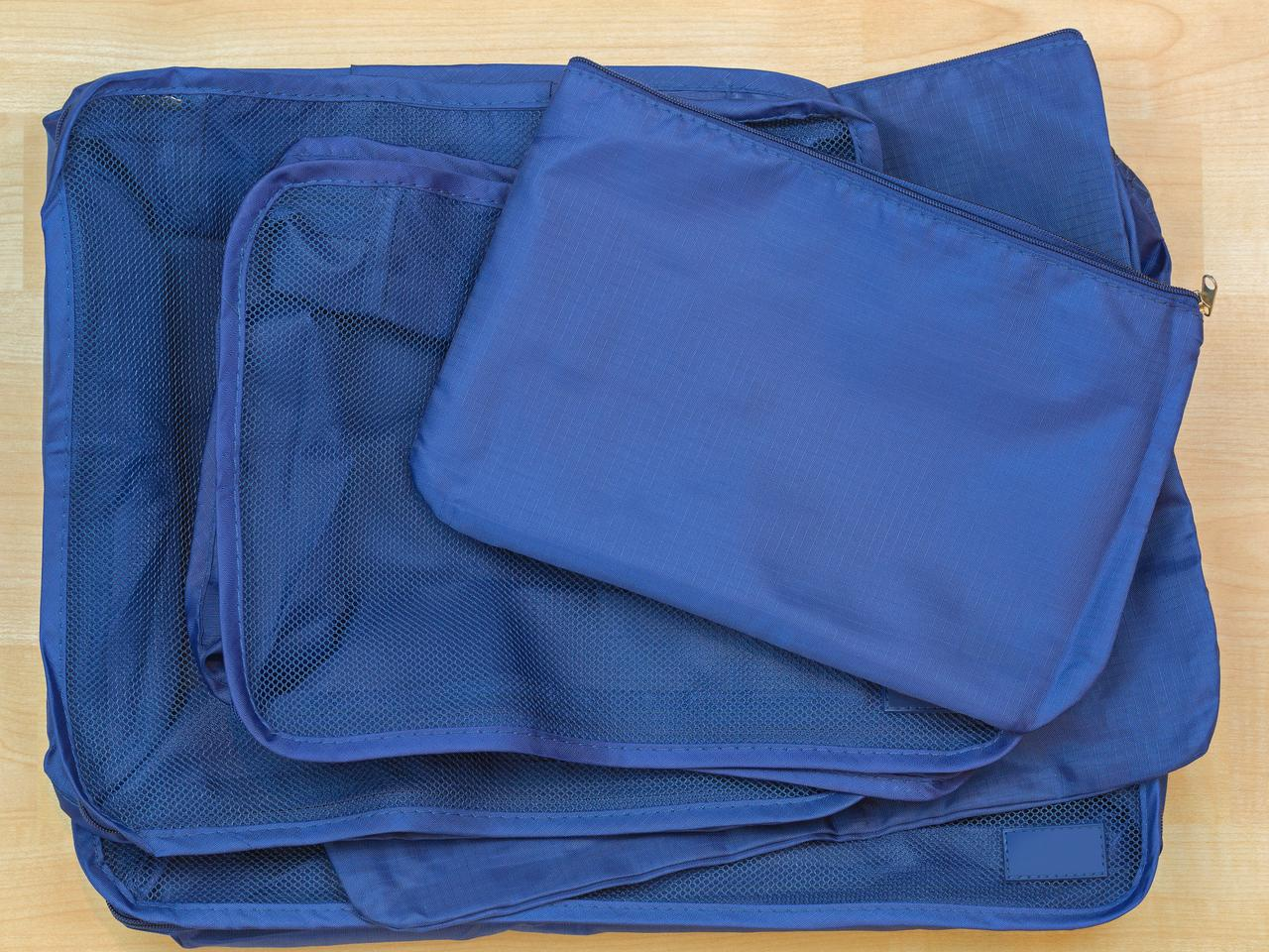 Different blue cube bags, set of travel organizer to help packing luggage easy, well organized