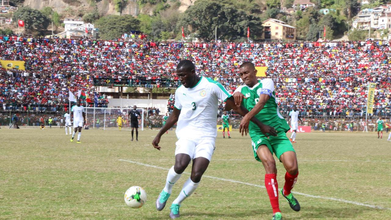 Senegal Kalidou Koulibaly (L) and Madagascar captain Andriatsima Fanev Ima (R) vie for the ball as the game went on after the tragedy