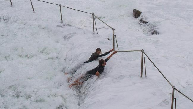 Two teenagers ignore the storm warnings, by risking their lives at Bronte Beach, Sydney, Australia. Picture: Bill Morris