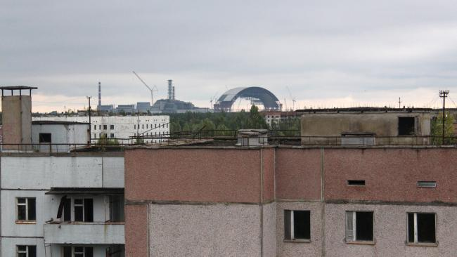 A view from 2013 across Pripyat rooftops towards the Chernobyl Nuclear Power Plant. The New Arch is still under construction, while the old sarcophagus enclosing Reactor Block 4 stands to its left. Picture: Darmon Richter/FUEL Publishing