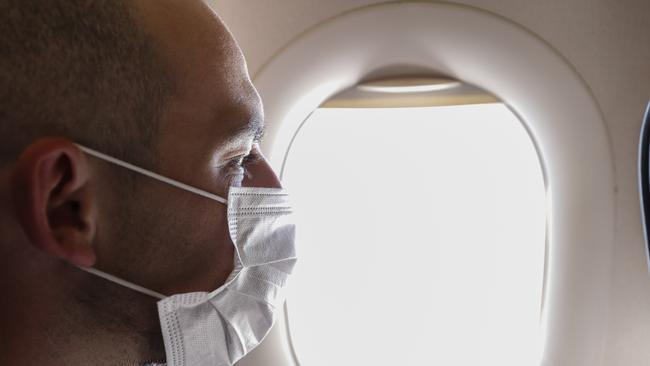 Portrait of adult man on wearing disposable raspiratory face mask for coronavirus protection, flying home on the evacuation plane, looking at porthole. Close up, copy space, background.
