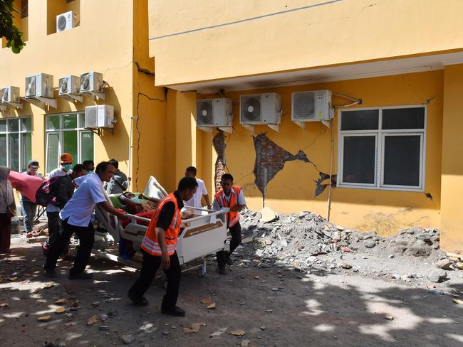 A man is wheeled passed a damaged wall to a makeshift ward. Picture: AFP