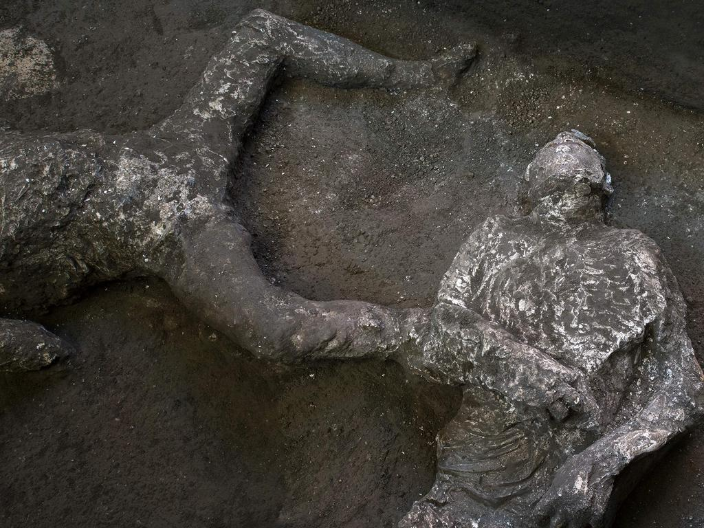 """This undated photo handout on November 21, 2020 by the Pompeii Archaeological Park shows casts of the bodies of two men, a 40-year-old master and his young slave, after they were found during recent excavations of a Villa in Civita Giuliana in the outskirts of Pompeii, as Park officials said conditions were optimal to get casts of the victims, following the technique perfected in 1863 by Giuseppe Fiorelli. - The ancient Roman city of Pompeii was engulfed under a hail of volcanic ash after nearby Mount Vesuvius erupted in the year 79. Vesuvius' eruption covered the in a toxic, metres-thick layer of volcanic ash, gases and lava flow which then turned to stone, encasing the city, allowing an extraordinary degree of frozen-in-time preservation both of city structures and of residents unable to flee. (Photo by Handout / POMPEI ARCHAEOLOGICAL PARK / AFP) / RESTRICTED TO EDITORIAL USE - MANDATORY CREDIT """"AFP PHOTO / POMPEII ARCHAEOLOGICAL PARK / LUIGI SPINA"""" - NO MARKETING - NO ADVERTISING CAMPAIGNS - DISTRIBUTED AS A SERVICE TO CLIENTS"""