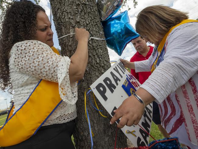Tanya Diaz, Brock Sanchez and Lucy Martines of League City place flowers, a sign and balloons on a tree outside of Santa Fe High School. Picture: AP