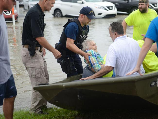 This August 14, 2016 US Coast Guard handout photo shows Coast Guard Chief Petty Officer Jon Tatroe evacuating people from a flooded assisted living home in Baton Rouge, Louisiana. Picture: AP.