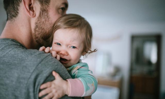 Cold and flu season takes its toll, with babies and small children even more susceptible to illness.  A dad holds his baby girl, trying to comfort her in the midst of her sickness.