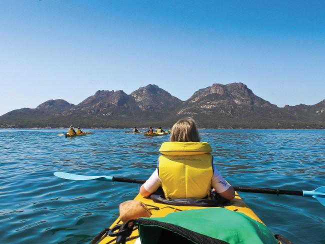 Kayak the Freycinet Peninsula The quaint coastal town of Coles Bay sits in the shadows of the spectacular Hazards mountain range. It's also the unofficial launching pad for those looking to explore Freycinet National Park or Wineglass Bay. The Freycinet Paddle is a three-hour guided kayak adventure designed as the perfect way to tour the best parts of the national park. Dual paddle kayaks and gentle water make this adventure perfect for all ages and abilities.Freycinet Adventures. Credit: Kathryn Leahy