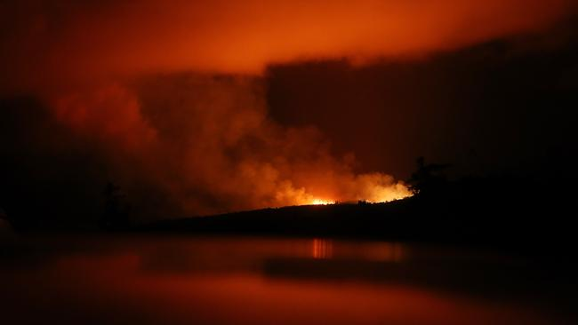 The latest Kilauea volcano activity illuminates the sky and is reflected off a vehicle (Bottom) on Hawaii's Big Island. Picture: Getty