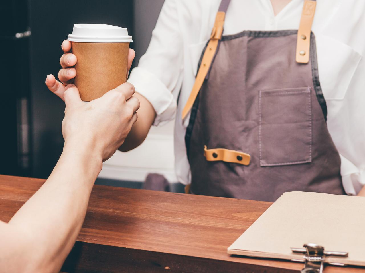 Woman barista giving coffee cup to customer at cafe
