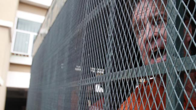 Australian filmmaker James Ricketson in a prison truck as he arrived at the municipal court in Phnom Penh. Picture: AP.