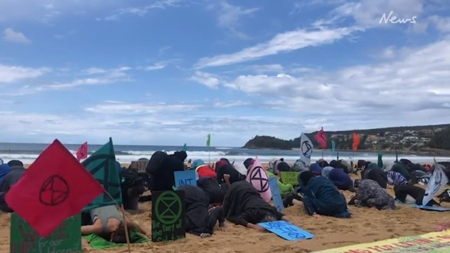 Extinction Rebellion protesters bury their heads in the sand on Manly Beach