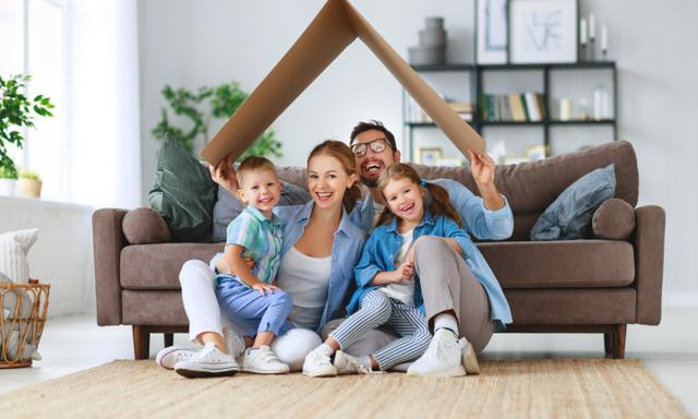 concept of housing and relocation. happy family mother father and kids with roof at a  home