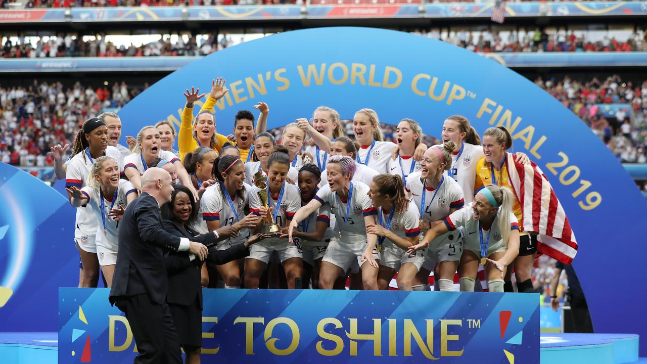 LYON, FRANCE - JULY 07: FIFA Secretary General, Fatma Samoura, and FIFA President, Gianni Infantino present the USA team with the FIFA Women's World Cup Trophy following their victory in the 2019 FIFA Women's World Cup France Final match between The United States of America and The Netherlands at Stade de Lyon on July 07, 2019 in Lyon, France. (Photo by Elsa/Getty Images)