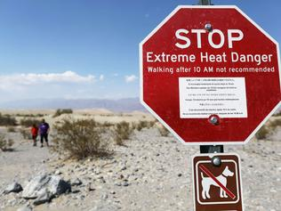 DEATH VALLEY NATIONAL PARK, CALIFORNIA - AUGUST 17: Visitors walk near a sign warning of extreme heat danger on August 17, 2020 in Death Valley National Park, California. The temperature reached 130 degrees at Death Valley National Park on August 16, hitting what may be the hottest temperature recorded on Earth since at least 1913, according to the National Weather Service. Park visitors have been warned, 'Travel prepared to survive.'   Mario Tama/Getty Images/AFP == FOR NEWSPAPERS, INTERNET, TELCOS & TELEVISION USE ONLY ==