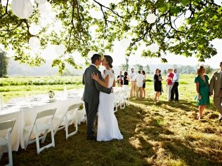 Bride and groom embracing about to kiss near banquet table set for dinner guests in background