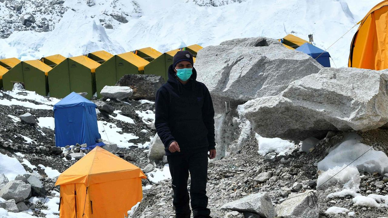 A expedition base camp staff wearing a face mask walks around Everest base camp where COVID-19 has now infiltrated. (Photo by PRAKASH MATHEMA / AFP).