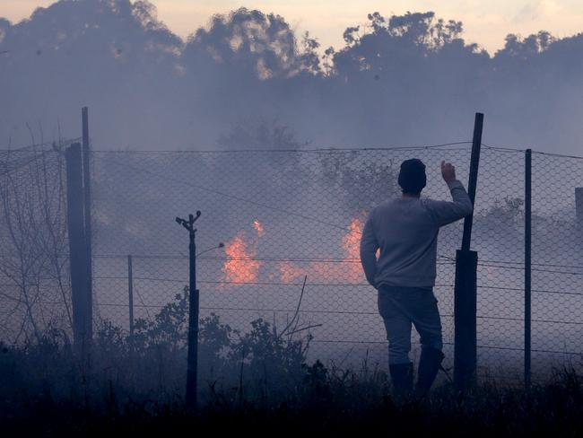 A resident watches the bushfire approach his property at Salt Ash. Picture: AAP
