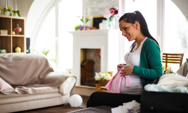 Pregnant mid adult woman packing suitcase for maternity hospital in the bedroom, holding baby clothes.