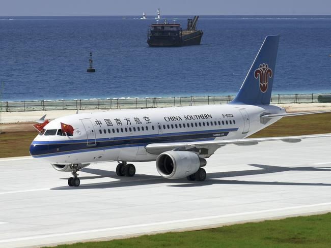 Pilots place Chinese national flags on the cockpit window of China Southern Airlines' passenger jet after it successfully test landed at an airport on the Meiji reef of the Nansha Islands in the South China Sea. Picture: Chen Yichen/Xinhua