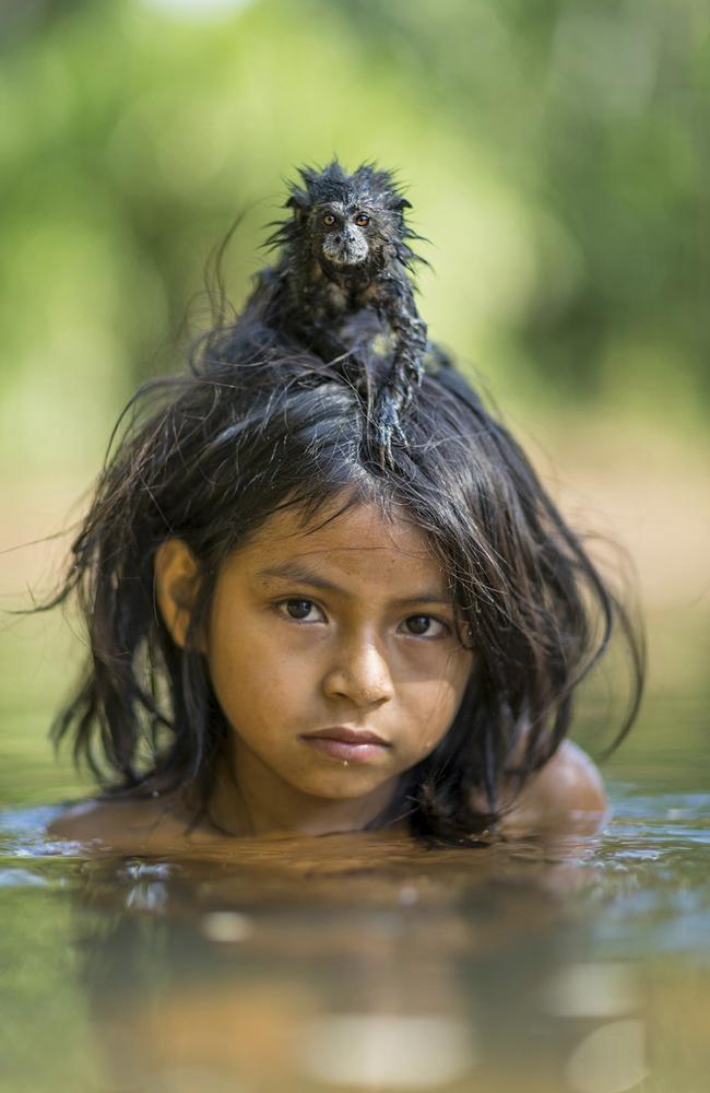 A pet saddleback tamarin hangs on to Yoina Mameria Nontsotega as the Matsigenka girl takes a dip in the Yomibato River, deep inside Peru's Manú National Park. Picture: Charlie Hamilton James/National Geographic