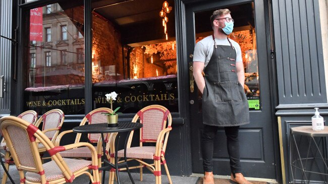 A bartender wearing a face mask stands outside a bar in Cardiff ahead of pubs, bars, restaurants and cafes shutting. Picture: Getty