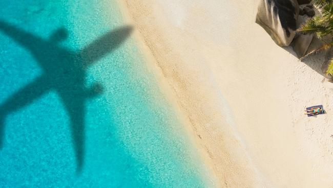 Concept of airplane travel to Exotic destination with shadow of commercial airplane flying above beautiful tropical beach. Beach holidays and travel. credit: istock