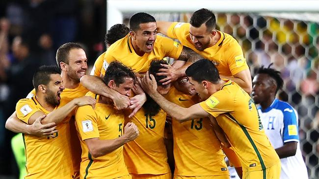 The Socceroos celebrate scoring a goal.