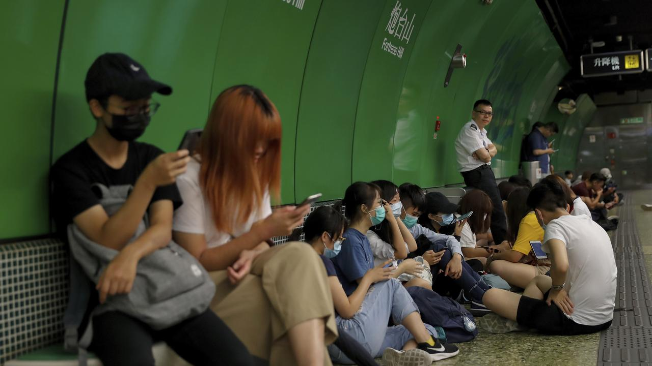 A man in a white uniform crosses his arms as protesters sit on a platform at Fortress Hill MTR underground station in Hong Kong. Picture: AP