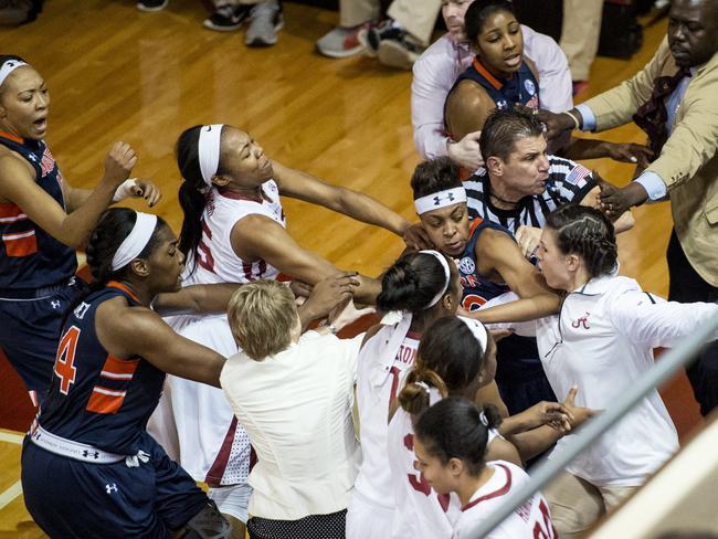 A fight between Auburn guard Hasina Muhammad, centre, facing camera, and Alabama guard Breanna Hayden (5) spills into the Alabama bench.