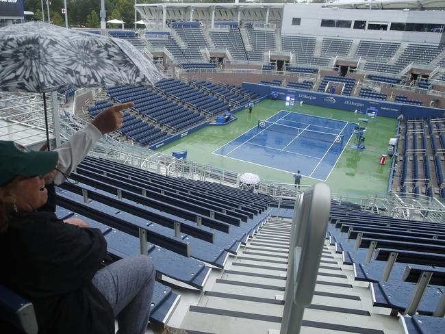 Tennis fans wait out a rain delay while sitting in Grandstand Stadium.