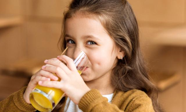 adorable kid drinking orange juice in cafe and looking at camera