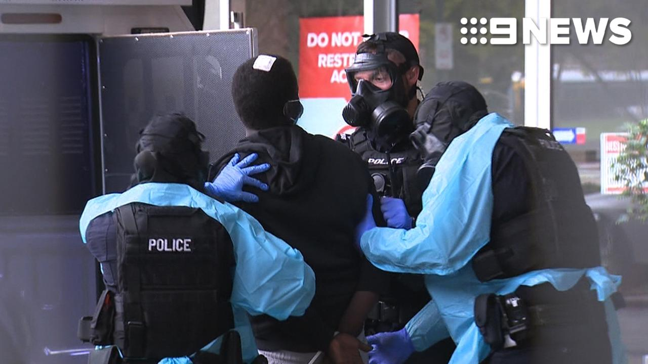 SA Police in gas masks escort a Victorian man from an Adelaide medi-hotel.