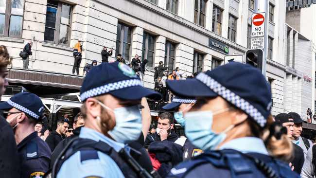 Protesters climb the awning at Sydney Town Hall during the 'World Wide Rally For Freedom' anti-lockdown rally. Picture: NCA