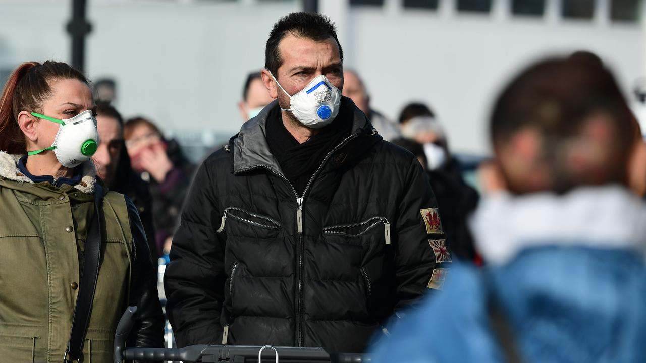Residents wearing a respiratory mask wait to be given access to shop in a supermarket in small groups of forty people in the small Italian town of Casalpusterlengo. (Photo by Miguel MEDINA / AFP)