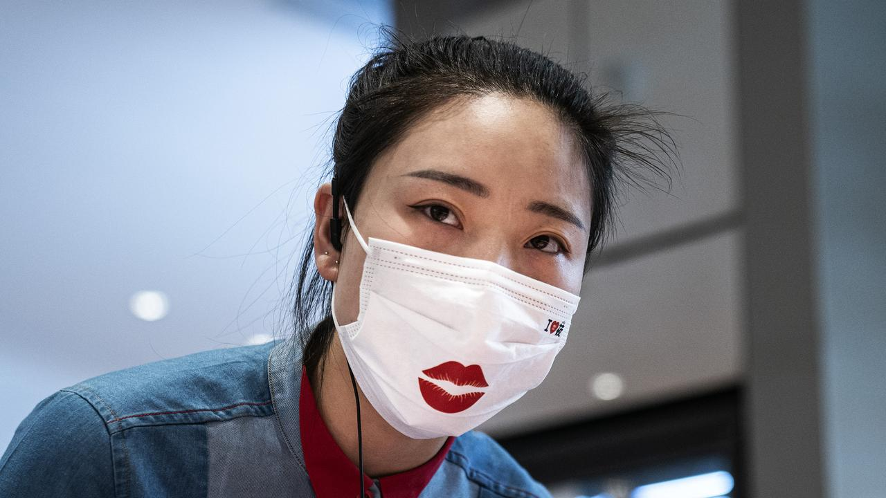 A waitress is pictured wearing a face mask while serving guests in Wuhan, more than a year after coronavirus emerged. Picture: Getty Images