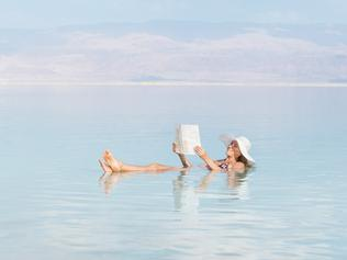 Relaxed woman reading newspaper while floating in Dead Sea water.