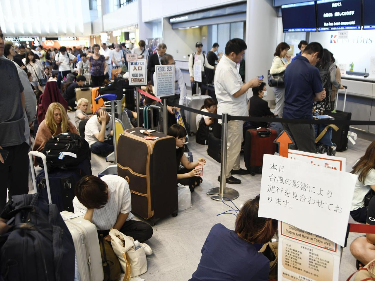 Travelers are stranded at Narita airport in Narita, near Tokyo Monday, Sept. 9, 2019 as railways and subway operators suspended services following a typhoon. Typhoon Faxai blew across the Tokyo metropolitan area Monday morning, causing dozens of injuries, while disrupting rush-hour travel and knocking out power. (Kyodo News via AP)