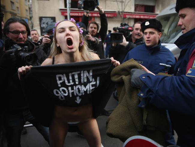 A bare-breasted Femen protester demonstrates against the scheduled visit of Russian President Vladimir Putin moments before she was detained by police near the Parliament building on February 17, 2015 in Budapest, Hungary. Picture: Sean Gallup