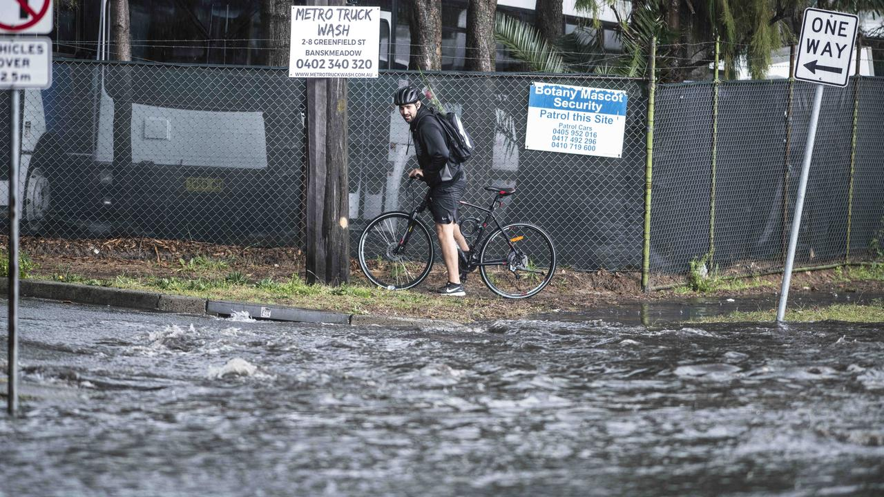 A cyclist considers his chances near a flooded street. Picture: Darren Leigh Roberts