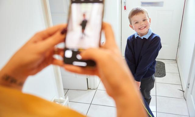 Smiling toddler ready for his first day at school having his picture taken